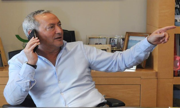 Samih Sawiris, Egyptian billionaire construction tycoon speaks in his mobile phone before an interview with Reuters to discuss his investment plans and outlook for the economy since the flotation of the pound in Cairo, Egypt February 21, 2017. Picture tak