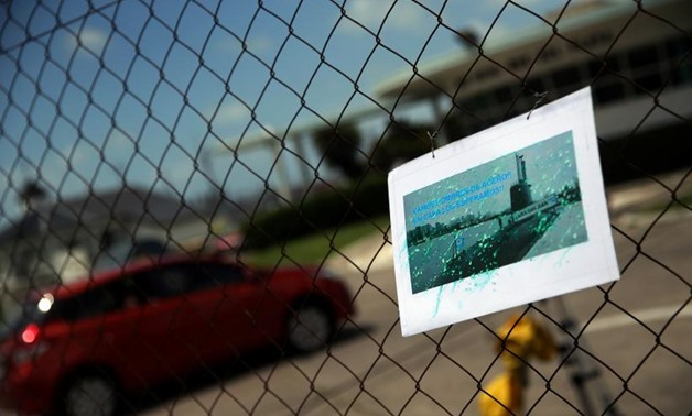 A car enters the Argentine Naval Base where the missing at sea ARA San Juan submarine sailed from as a picture of it hangs on a fence in Mar del Plata, Argentina November 19, 2017. REUTERS/Marcos Brindicci