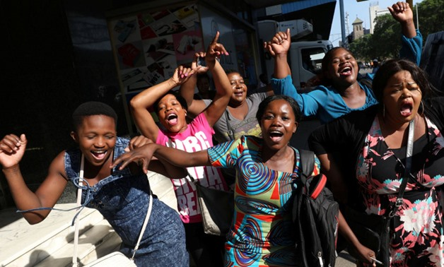 Zimbabweans celebrate in the morning sun after President Robert Mugabe resigned in Harare - REUTERS