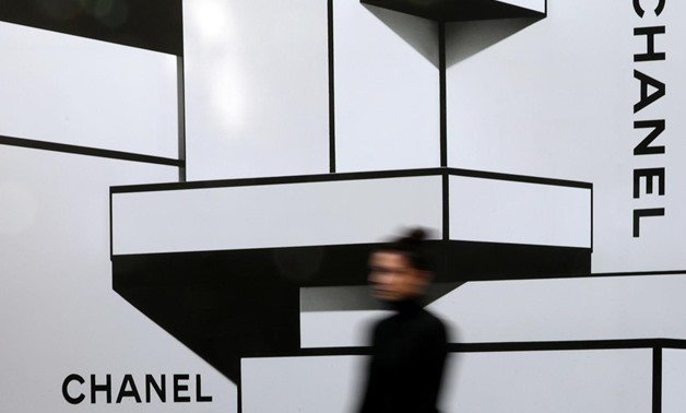 A woman walks past a wall with logos of French luxury goods maker Chanel in Nice, France, February 22, 2017. REUTERS/Eric Gaillard/File Photo
