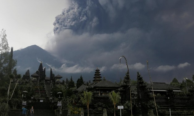 Foreign tourists take pictures as Mount Agung erupts at Besakih Temple in Karangasem, Bali, Indonesia on November 26, 2017. REUTERS/Johannes P. Christo