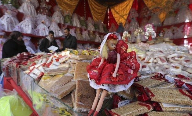 A man sells traditional doll toys and sweets for children to celebrate the birthday of Prophet Mohamed, which will fall next week, in a makeshift tent in Cairo, December 30, 2014 – REUTERS / Mohamed Abd El Ghany