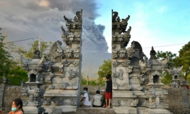 © AFP / by Sonny Tumbelaka | Balinese people look at Mount Agung during an eruption seen from Kubu sub-district in Karangasem Regency on Indonesia's resort island of Bali on November 26, 2017