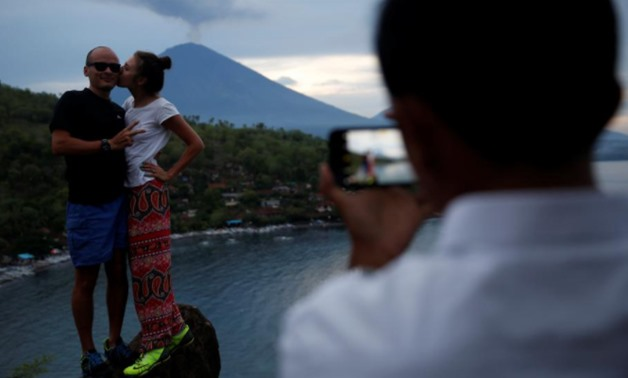 Tourists from Russia pose while having their photograph taken with Mount Agung volcano erupting in the background from Amed, Karangasem Regency, Bali, Indonesia, November 30, 2017. REUTERS/Darren Whiteside