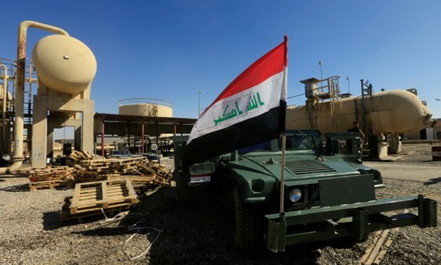 An Iraqi flag is seen on a military vehicle at an oil field in Dibis area on the outskirts of Kirkuk - REUTERS