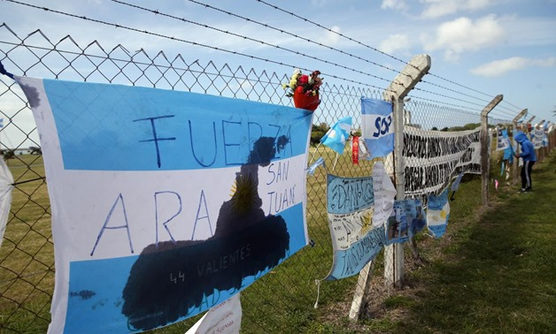 A bouquet of flowers is seen placed next to banners in support of the 44 crew members of the missing at sea ARA San Juan submarine, on a fence outside an Argentine naval base in Mar del Plata, Argentina November 24, 2017. REUTERS/Marcos Brindicci