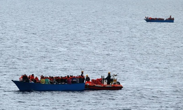 Migrants on wooden boats in the Mediterranean Sea off the coast of Libyam - Reuters Photo