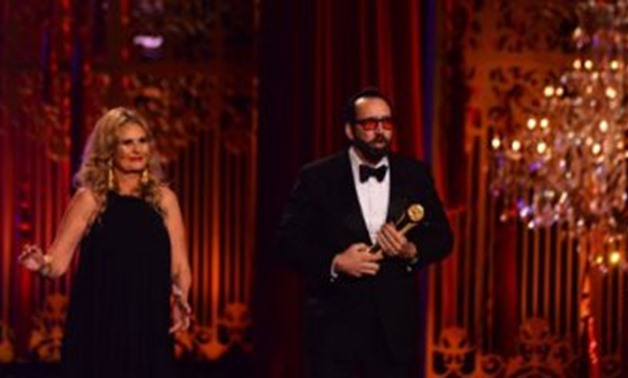 Nicolas Cage after receiving his award from Yousra at CIFF's closing ceremony on November 30 - Egypt Today