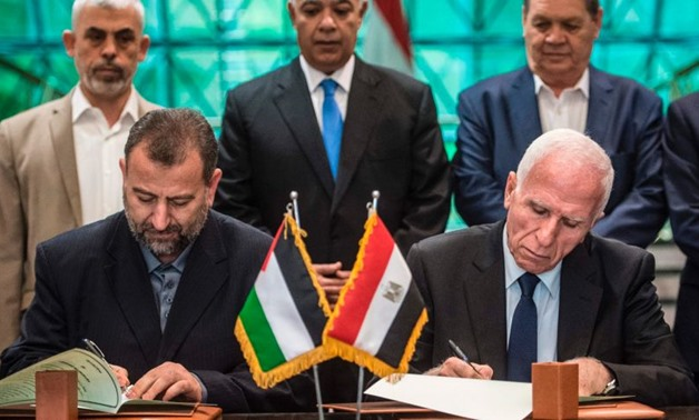Fatah's Azam al-Ahmad (R)and Saleh al-Arouri of Hamas (L) sign a reconciliation deal at the Egyptian intelligence services headquarters in Cairo on October 12, 2017 – AFP