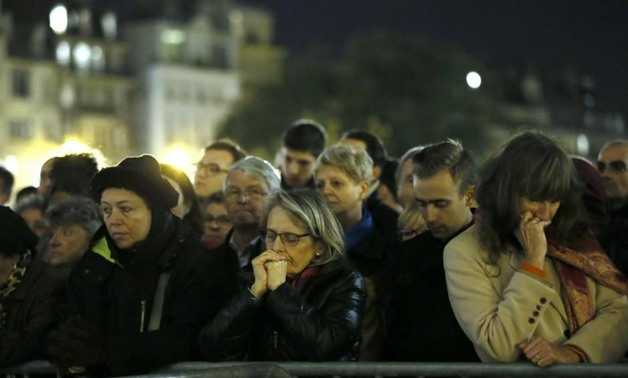 People gather outside Notre Dame Cathedral where a mass is held following a series of deadly attacks in Paris, November 15, 2015 - REUTERS