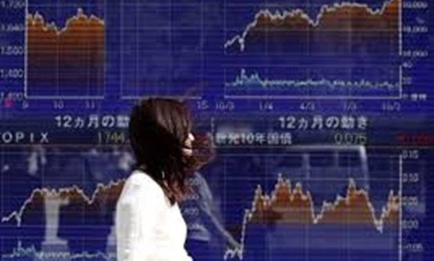 A woman walks in strong wind caused by Typhoon Lan, past an electronic board showing the graphs of the recent movements of Japan's Nikkei average outside a brokerage in Tokyo, Japan, October 23, 2017. REUTERS/Issei Kato