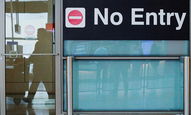 FILE PHOTO: International travelers (reflected in a closed door) arrive on the day that U.S. President Donald Trump's limited travel ban, approved by the U.S. Supreme Court, goes into effect, at Logan Airport in Boston, Massachusetts, U.S., June 29, 2017.