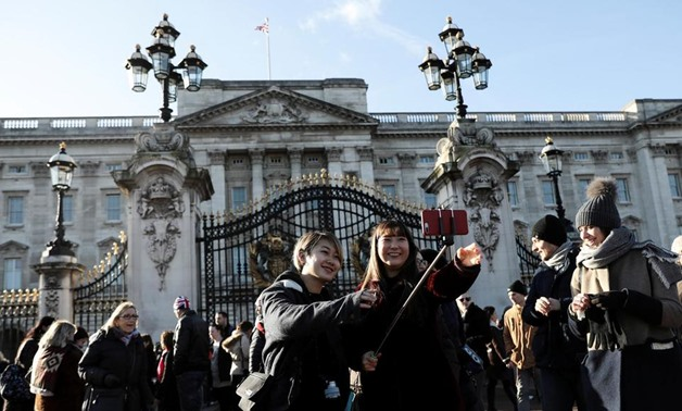 Tourists poses for selfie photographs outside Buckingham Palace in London. The UK capital was again the top pick in Europe for tourist arrivals - Reuters/Simon Dawson