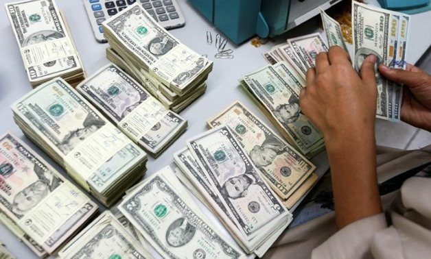REUTERS- A bank employee counts U.S. dollar notes