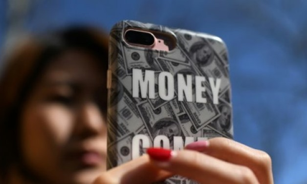 © AFP / by Ryan MCMORROW | Smartphones have made it even easier for consumers to borrow cash in China and a number of online platforms have listed publicly in the US this year