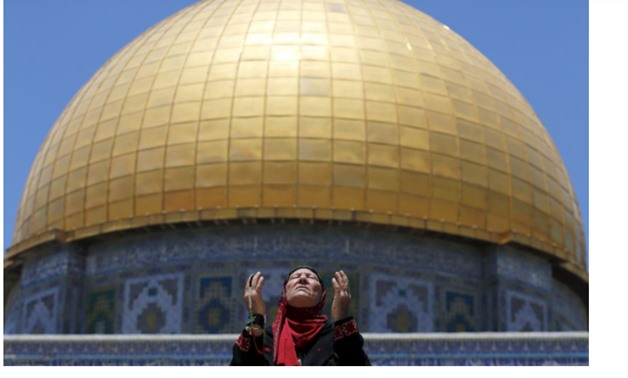 A Palestinian woman prays in front of the Dome of the Rock on the first Friday of the holy month of Ramadan at the compound known to Muslims as the Noble Sanctuary and to Jews as Temple Mount, in Jerusalem's Old City June 19, 2015. REUTERS/Ammar Awad/File