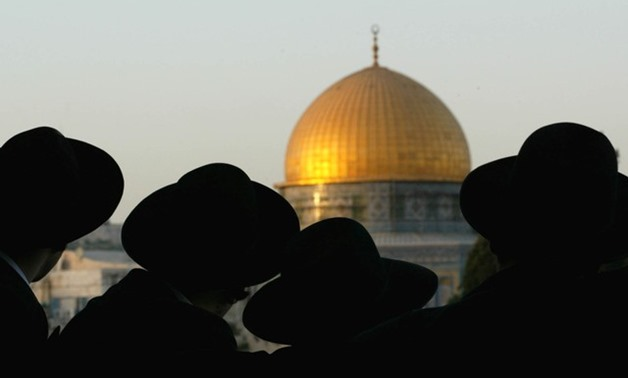 Ultra-Orthodox Jews look at the Dome of the Rock in the Old City during a demonstration of some 200 right-wing Israelis in Jerusalem on August 8, 2002. REUTERS/Oleg Popov/File Photo