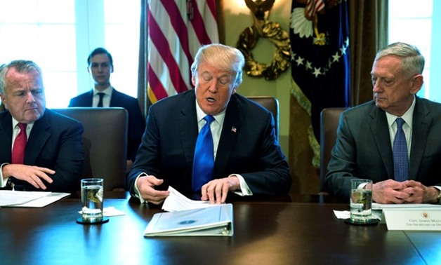 U.S. President Donald Trump, flanked by Deputy Secretary of State John Sullivan (L) and Defense Secretary James Mattis (R), speaks to reporters before he holds a cabinet meeting at the White House in Washington, U.S. December 6, 2017. REUTERS/Jonathan Ern