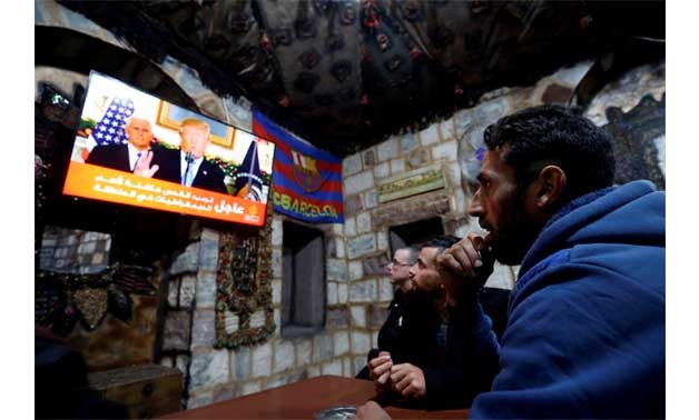 Palestinians in the West Bank city of Nablus watch on December 6 a televised broadcast of U.S. President Donald Trump - REUTERS/Abed Omar Qusini