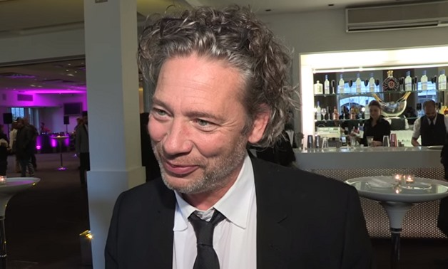 Screencap of Dexter Fletcher conducting an interview with PremiereScene, December 7, 2017 – YouTube/PremiereScene
