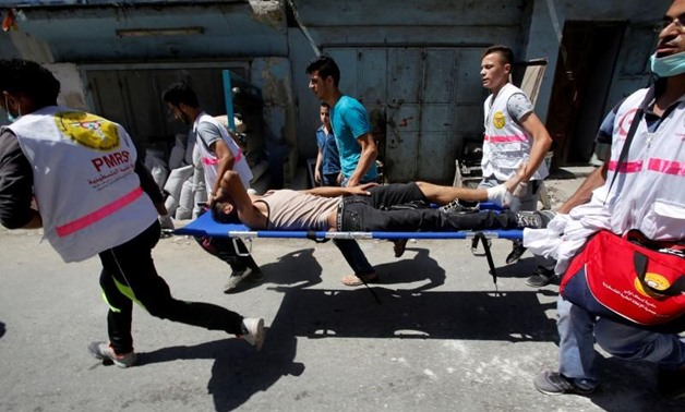 Medics carry an injured Palestinian during clashes with Israeli troops in the West Bank Al-Fawwar refugee camp, south of Hebron August 16, 2016. REUTERS/Mussa Qawasma