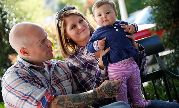 DOING WELL: Father Donnie Gooding and mother Katy Yeager play with their daughter, Kennedy. Almost a year has passed since Kennedy was born in drug withdrawal. Yeager, at risk of losing the baby, took a gamble on a new program for mothers battling addicti