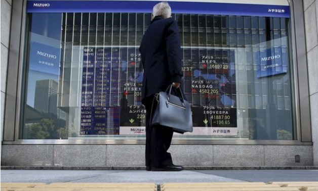 A pedestrian stands to look at an electronic board showing the stock market indices of various countries outside a brokerage in Tokyo, Japan, February 26, 2016 -  REUTERS/Yuya Shino