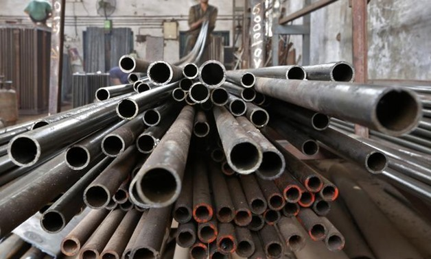A worker stacks steel pipes in Ahmedabad November 4, 2014. REUTERS/Amit Dave/File Photo