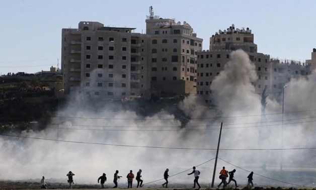 Palestinian protesters run away from tear gas fired by Israeli troops during clashes near the Jewish settlement of Bet El, near the West Bank city of Ramallah November 13, 2015. REUTERS/Mohamad Torokman