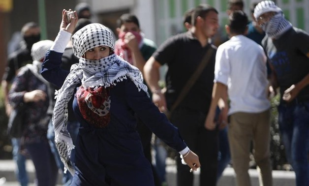 A Palestinian woman hurls stones at Israeli troops during clashes in the West Bank city of Hebron October 13, 2015. REUTERS/Mussa Qawasma