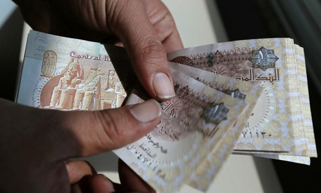 A man counts Egyptian notes outside bank in Cairo, Egypt October 24, 2016. REUTERS-Mohamed Abd El Ghany