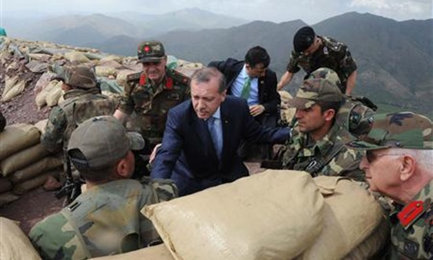 Turkish President Tayyip Erdogan (C) speaks with Turkish soldiers in a trench during his visit to the Turkish city of Hakkari at the border with Iraq June 20, 2010. REUTERS/Kayhan Ozer/Anatolian