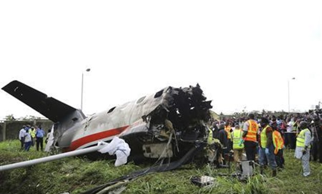 FILE- Rescue workers stand near the tail of a plane at the site of a plane crash near the Lagos international airport October 3, 2013. REUTERS/Akitnunde Akinleye