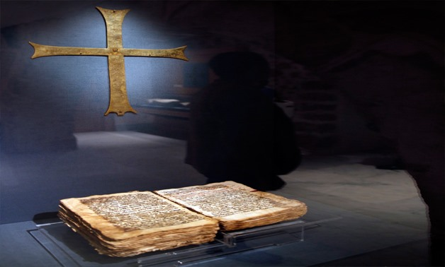 FILE- A man is reflected on the glass which contains a Christian manuscript and a cross at Saint Catherine's monastery, in the Sinai Peninsula, south of Egypt, December 8, 2015. Picture taken December 8, 2015. REUTERS/Amr Abdallah Dalsh      TPX IMAGES OF