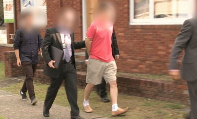 AFP officers arrest a 59-year-old Chan Han Cho who had been living in Australia for more than 30 years. Photograph: Australian federal police