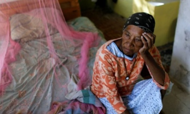 © AFP | Aurea Cruz, 66, sits on her bed inside her house damaged by Hurricane Maria in Vieques, Puerto Rico