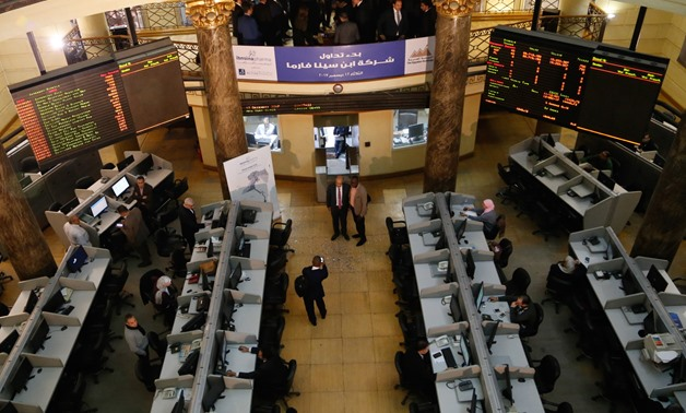 FILE- Employees in the EGX following performance of the trading session