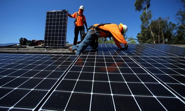 Solar installers from Baker Electric place solar panels on the roof of a residential home in California, U.S. October 14, 2016- Reuters