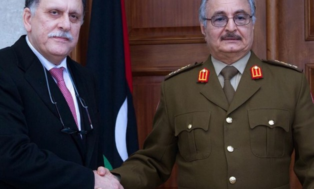 General Khalifa Haftar (R), commander of the armed forces loyal to the internationally recognized Libyan government, shakes hands with the head of the UN backed Libyan Presidential Council, Fayez al-Sarraj, in 2016- AFP
