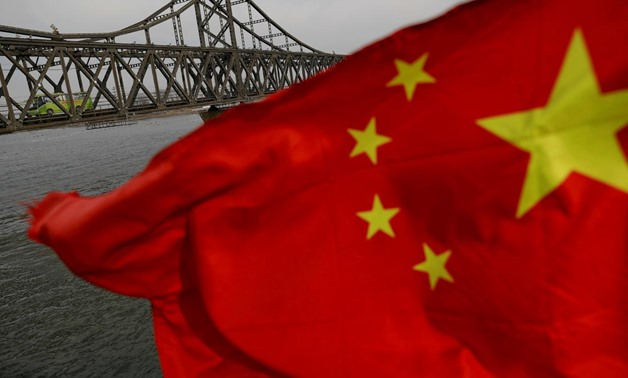 A Chinese flag is seen in front of the Friendship bridge over the Yalu River connecting the North Korean town of Sinuiju and Dandong in China's Liaoning Province on April 1, 2017. REUTERS/Damir Sagolj/File Photo