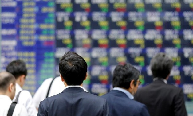 FILE PHOTO: People walk past an electronic stock quotation board outside a brokerage in Tokyo, Japan, September 22, 2017. REUTERS/Toru Hana