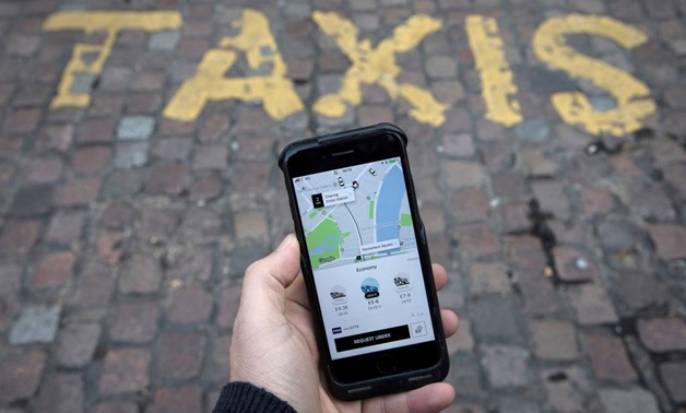 FILE PHOTO: A photo illustration shows the Uber app on a mobile telephone, as it is held up for a posed photograph, in London, Britain November 10, 2017. REUTERS/Simon Dawson