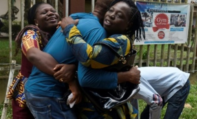 © AFP / by Sophie BOUILLON | A returnee migrant (C) brought home from Libya is embraced by relatives in Benin, capital of Edo State in midwest Nigeria on December 7, 2017. Out of over 400 Nigerian migrants that voluntarily returned from Libya, more than h