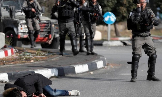 A Palestinian man lies on the ground after being shot by Israeli border policemen near the Jewish settlement of Beit El, near the West Bank city of Ramallah December 15, 2017 REUTERS