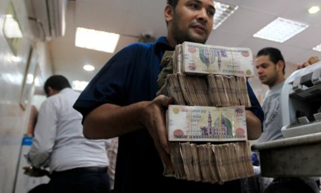 An employee carries money at an exchange office in downtown Cairo – Reuters/Amr Dalsh