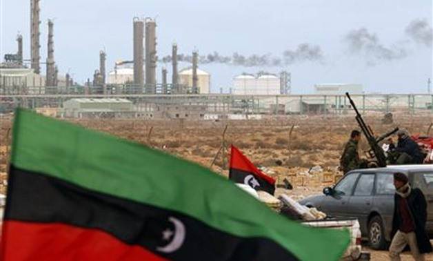 The Kingdom of Libya flag flies in front of a refinery in Ras Lanuf in this March 8, 2011, file photo. REUTERS/Goran Tomasevic