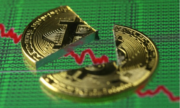 Broken representation of the Bitcoin virtual currency, placed on a monitor that displays stock graph and binary codes, are seen in this illustration picture, December 21, 2017 - REUTERS/Dado Ruvic/Illustration