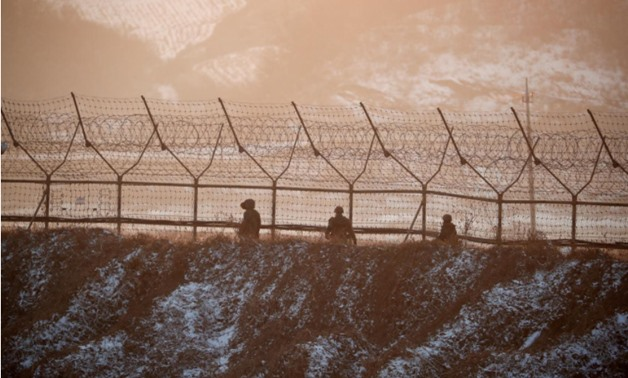 South Korean soldiers patrol along a barbed-wire fence near the militarized zone separating the two Koreas, in Paju, South Korea, December 21, 2017 - REUTERS/Kim Hong-Ji