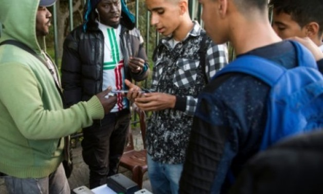 AFP / by Sophie Pons | Migrants sell mobile telephones from a street stall in the Moroccan capital on December 19, 2017