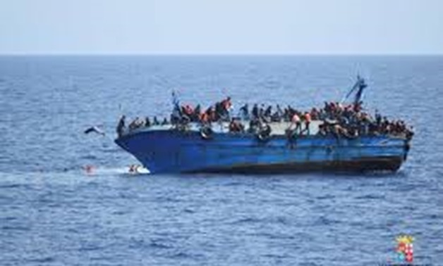 "Migrants are seen on a capsizing boat before a rescue operation by Italian navy ships ""Bettica"" and ""Bergamini"" (unseen) off the coast of Libya in this handout picture released by the Italian Marina Militare on May 25, 2016. Marina Militare/Handout via RE"